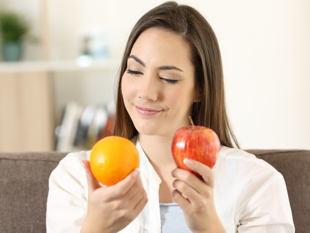 Young woman considering apple vs orange