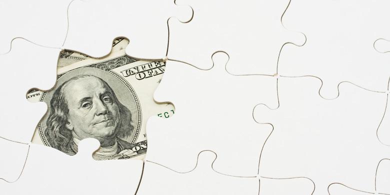 benjamin franklin $100 peering through puzzle piece